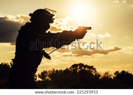 Silhouette of police officer with pistol at sunset