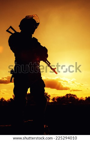 Silhouette of police officer with weapons at sunset - stock photo