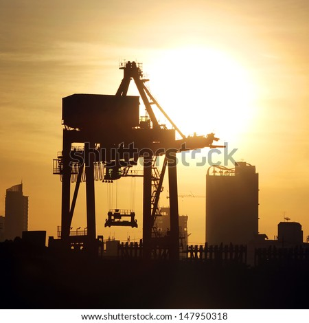 Silhouette of port warehouse with container cargo and crane bridge - stock photo