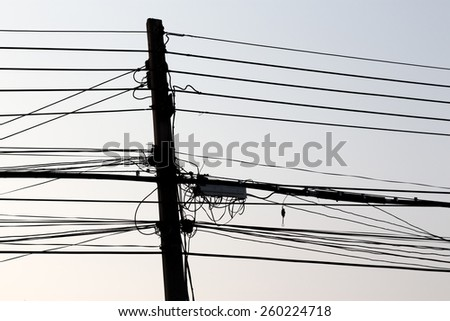 Silhouette of power and telephone cables on a concrete mast