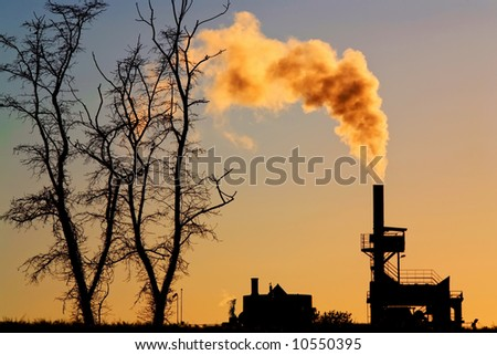 silhouette of power plant with smoke at dusk and dead tree, global warming