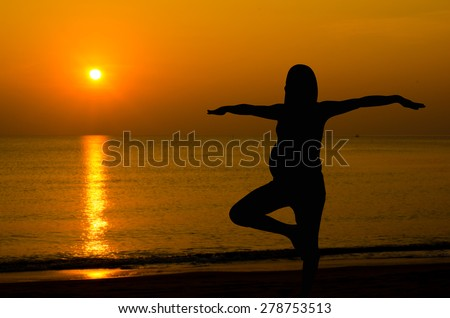 Silhouette of pregnant doing yoga on the beach in morning