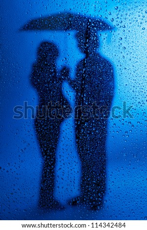 Silhouette of pregnant lady and husband standing under umbrella over blue background
