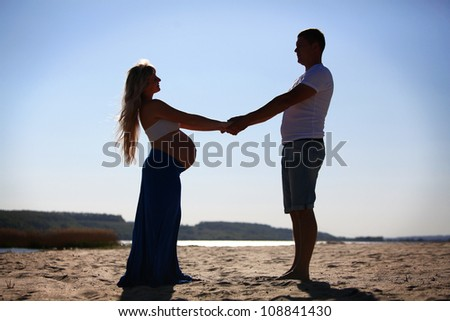 Silhouette of pregnant woman and man - stock photo