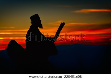 silhouette of priest reading from the holy bible in the sunset light, Romania, Ceahlau - stock photo