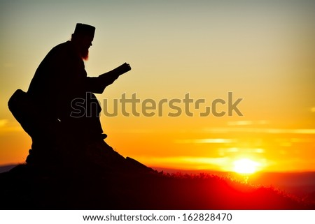 silhouette of priest reading in the sunset light - stock photo