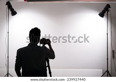 Silhouette of professional photographer working in the studio - stock photo