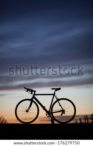 silhouette of race bike in sunset  - stock photo