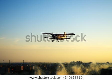 Silhouette of red vintage airplane flying over town in the sunset - stock photo