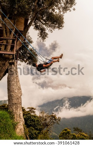 Silhouette Of Relaxing Teenager Man On A Swing, Casa Del Arbol, The Tree House, Tungurahua Volcano Powerful Explosion On March 2016 In The Background, Ecuador, South America  - stock photo