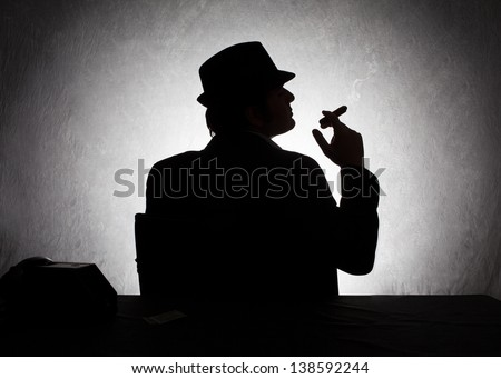 silhouette of retro style gangster holding his cigar on grunge background - stock photo