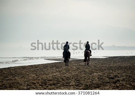 Silhouette of Riders at the beach riding horses