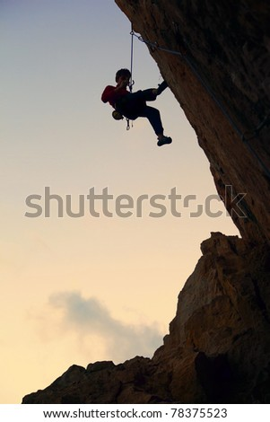 Silhouette of rock climber against sky background