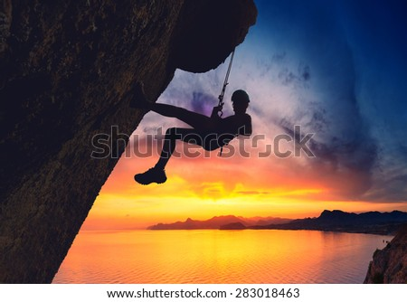 Silhouette of rock climber against sunset over the sea sunset background