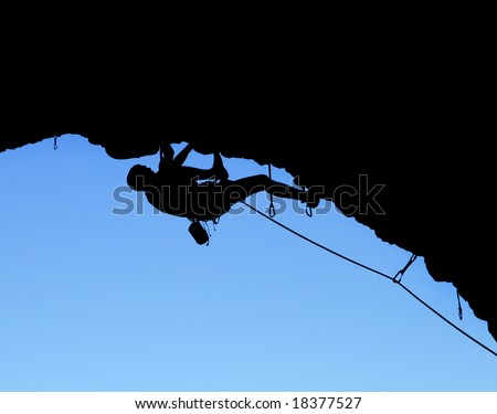 silhouette of rock climber climbing on a steep cliff - stock photo