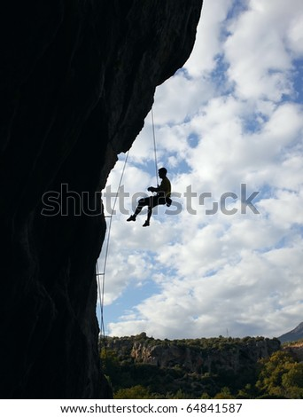 Silhouette of rock climber going down after reaching the top of the route with cloudy sky background