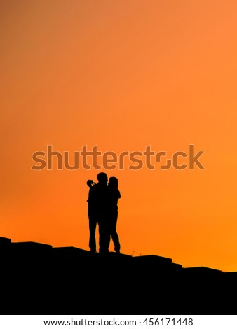 Silhouette of romantic couple in a park at sunset