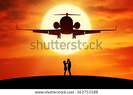 Silhouette of romantic couple standing on the hill under a flying aircraft at sunset time