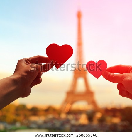 silhouette of romantic lovers hand hold love heart paper with eiffel tower in Paris with sunset - stock photo