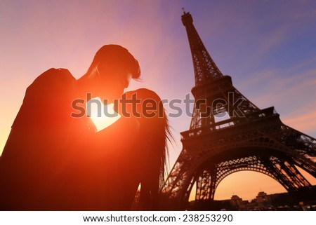 silhouette of romantic lovers with eiffel tower in Paris with sunset - stock photo