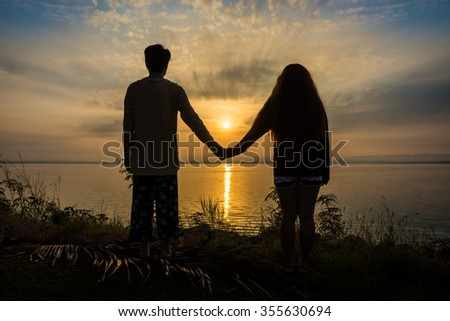 Silhouette of romantic young Asian couple holding hands looking in the sunset or sunrise on bank. Scenery of Pa Sak Chonlasit lake, Lopburi province, Thailand. - stock photo