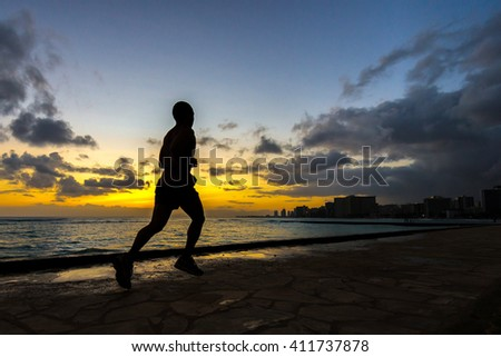 Silhouette of runner jogging along Waikiki beach at sunset golden hour - stock photo