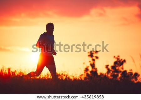 Silhouette of runner. Outdoor cross-country running. Athletic young man is running in the nature during golden sunset. - stock photo