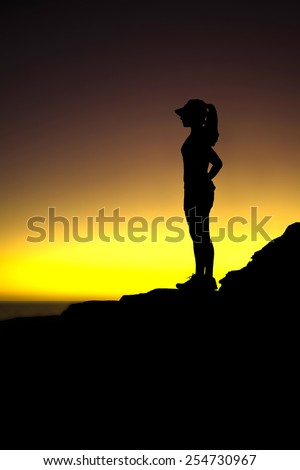 Silhouette of runner wearing a hat, taking a rest break during sunset at the top of ocean side trail