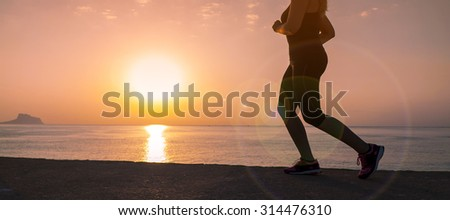 Silhouette of running female athlete on sunset/sunrise seaside background, concept of endurance, strength, healthy lifestyle