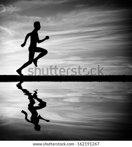 Silhouette of running man against sky. Silhouette of man running at sunset. Water reflection. Black and White. Element of design.