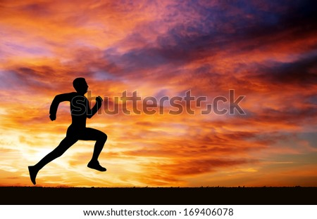 Silhouette of running man against the colorful sky. Silhouette of running man on sunset fiery background  - stock photo
