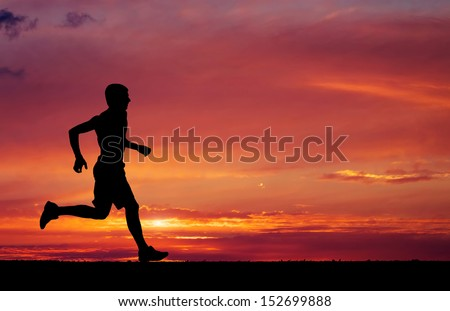 Silhouette of running man on sunset fiery background - stock photo