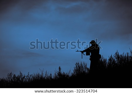 Silhouette of russia military soldier or officer with weapons at sunset - stock photo