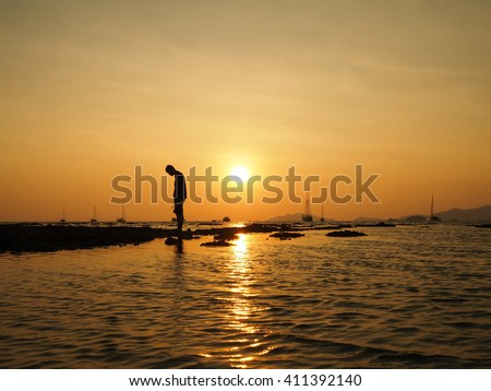 Silhouette of sad young man standing dejectedly turn back to the sun at sea beach with beautiful sky sunset background. - stock photo