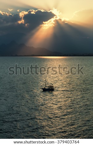 Silhouette of sailboat in Antalya bay, Turkey, at sunset with Bydaglari Mountains in the background.