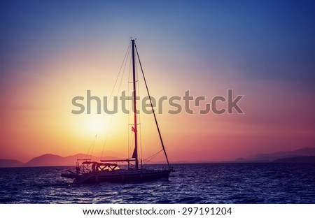 Silhouette of sailboat on sunset, water transport in bright yellow sun light, sea trip in the evening, traveling around Greek islands - stock photo