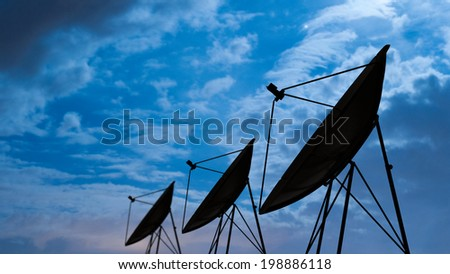 Silhouette of satellite dish in night sky - stock photo