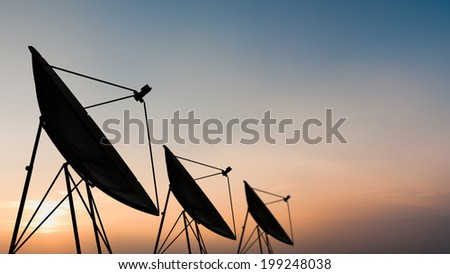 Silhouette of satellite dish in sunset sky - stock photo