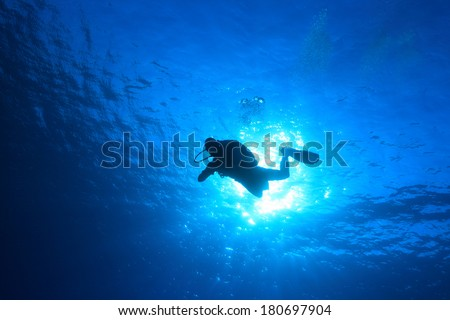 Silhouette of scuba diver and sunlight in the blue water - stock photo