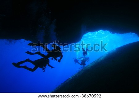Silhouette of scuba divers in an underwater cave - stock photo