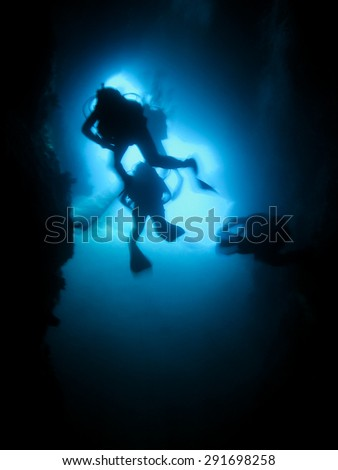 Silhouette of scuba divers in an underwater cave. Cave diving - stock photo
