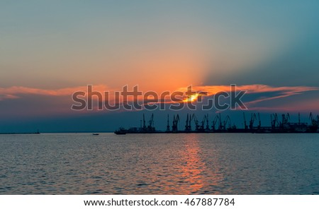 Silhouette of sea cargo port with cranes.