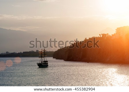Silhouette of ship on the sea near mountain at sunset - stock photo