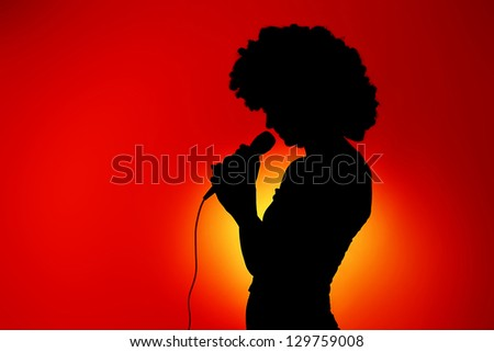 Silhouette of singing woman with microphone against red background - stock photo