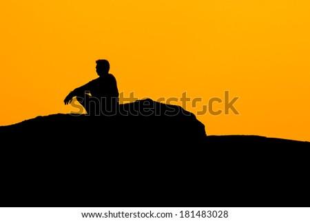 Silhouette of sitting man on sunset. - stock photo