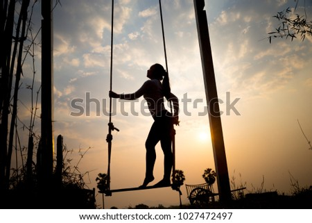 Silhouette of slimming woman post on swing over the sunrise in the morning.