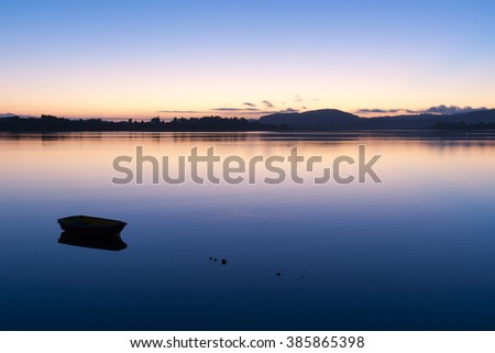 Silhouette of small boat afloat and distant hills across calm bay during brilliant sunrise.