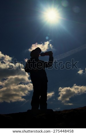 Silhouette of small boy drinks water from plastic bottle. Sunny colorful daybreak in rocky mountains. Children hiker stand on rock - stock photo