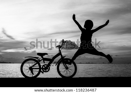 silhouette of small boy on bike at dusk.