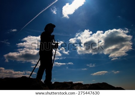 Silhouette of small boy with poles in hands. Sunny colorful daybreak in rocky mountains. Children hiker stand on rocky view point above misty valley.